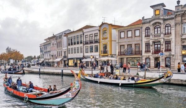 S자 모양의 운하가 도시를 관통하는 아베이루에서 곤돌라를 타는 관광객들.