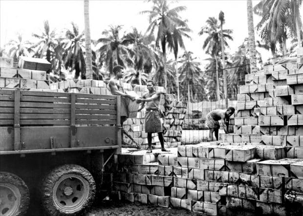 1944년 과달카날에서 미군에 보급될 맥주 상자를 내리는 솔로몬 제도의 주민들.  글항아리 제공