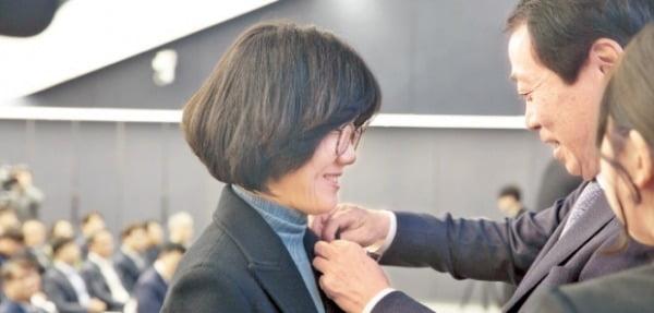 안병덕 코오롱 부회장(오른쪽)이 지난 2일 열린 그룹 통합 시무식에서 조은정 코오롱인더스트리 미래연구소 상무보에게 코오롱공감 '서핑 2020' 배지를 달아주고 있다.  코오롱 제공