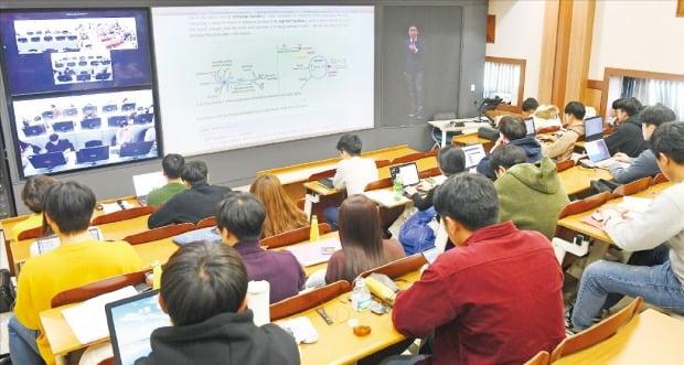 학생들이 강의실에서 텔레프레즌스로 강의를 듣는 모습. 화면 오른쪽엔 스튜디오에 있는 교수 모습이, 화면 중앙엔 강의자료, 화면 왼쪽엔 다른 강의실에서 수업을 듣는 학생들이 보인다.  /강은구 기자 egkang@hankyung.com