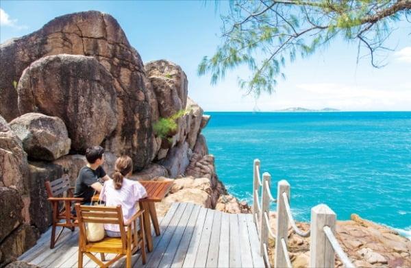 햇빛의 각도에 따라 회색과 오렌지색을 내는 화강암 해변에서 휴식을 취하고 있는 관광객.