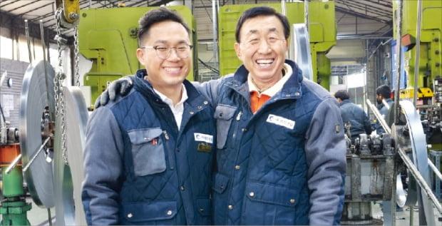 영진산업 창업주 민병오 회장(오른쪽)이 가정용 무볼트 선반 제조 현장에서 아들 민효기 대표의  어깨를 두르며 웃고 있다.  영진산업  제공