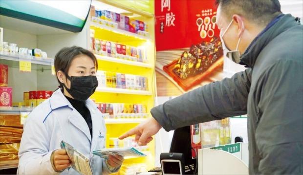 < 中 마스크 가격 10배 치솟아 > 신종 코로나바이러스(우한 폐렴)의 진원지인 중국 우한의 한 약국 직원이 22일 마스크를 판매하고 있다. 지난해 말 첫 발견 이후 이날까지 확진 환자가 473명으로 늘어나면서 마스크 가격이 열 배까지 치솟자 중국 정부는 마스크 가격 인상 금지 조치를 내렸다.  AP연합뉴스