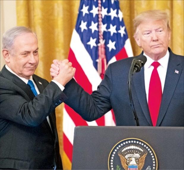 < 밀착 > 도널드 트럼프 미국 대통령(오른쪽)이 28일(현지시간) 백악관에서 중동평화구상을 발표하며 베냐민 네타냐후 이스라엘 총리와 굳게 손을 잡고 있다.   EPA연합뉴스