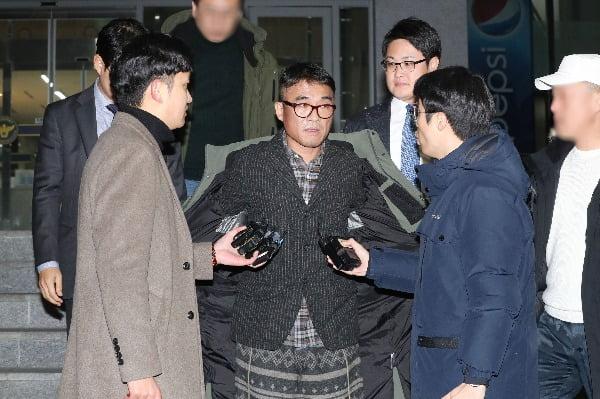 성폭행 혐의을 받는 가수 김건모가 피의자 조사를 마친 뒤 15일 오후 서울 강남경찰서를 빠져나온 뒤 취재진의 질문을 들으며 외투를 벗고 있다. 사진=연합뉴스