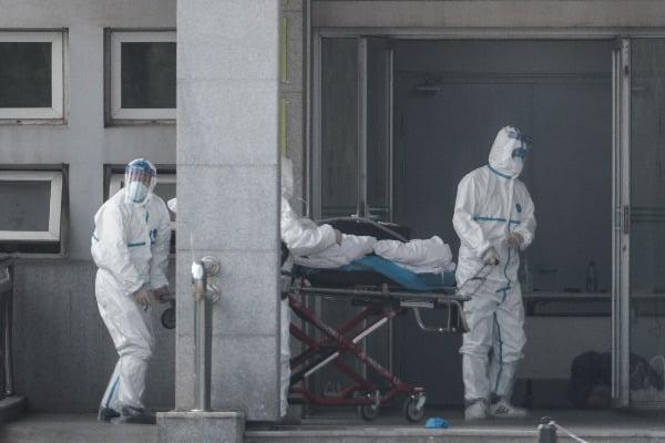 신종 코로나바이러스에 의한 폐렴이 발생한 중국 후베이성 우한에서 18일 의료진이 폐렴 환자들을 전담 치료하고 있는 현지 진인닌탄 병원으로 환자 1명을 후송하고 있다. EPA