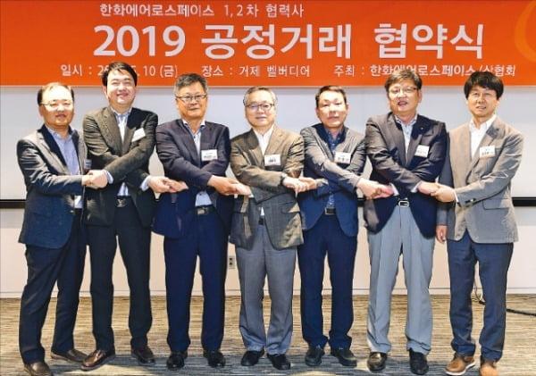 신현우 한화에어로스페이스 사장(가운데)과 협력사 경영진이 '2019년 공정거래 협약식'에서 손을 맞잡고 있다.  한화그룹 제공