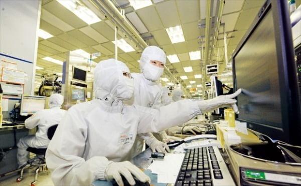 SK하이닉스 직원들이 경기 이천공장에서 반도체 생산 공정을 점검하고 있다.  한경DB