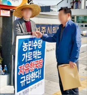 지난해 11월 여주시의회에서 자유한국당 의원들이 농민수당 도입을 반대하자 더불어민주당 관계자가 규탄 시위를 하고 있다.  한경DB