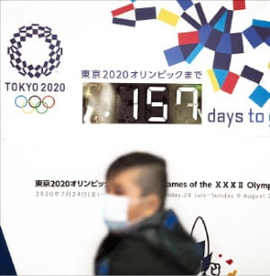 일본 도쿄에서 마스크를 쓴 시민이 올림픽 카운트다운 현황판 앞을 지나고 있다.  /AP연합뉴스