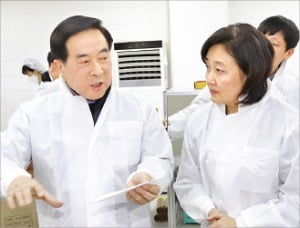 경기 안양에 있는 마스크 제조사 에버그린의 이승환 대표(왼쪽)가 박영선 중소벤처기업부 장관에게 마스크 제조 과정을 설명하고 있다.