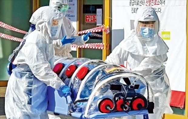 <대구 경북 의료진 초긴장 > 대구에서 신종 코로나바이러스 감염증(코로나19) 환자가 무더기로 나온 19일 경북대병원 의료진이 긴급 이송된 의심환자를 병원 안으로 옮기고 있다. 이날 대구·경북 지역에서는 20명의 확진자가 나왔다. 연합뉴스