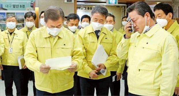 문재인 대통령이 25일 대구 남구청을 방문, 코로나19 확산에 따른 취약계층 복지전달체계 현황을 보고받은 뒤 조재구 남구청장(오른쪽)이 쓴 건의 편지를 읽고 있다. 조 구청장은 이날 눈물을 보이며 지원을 호소했다. /대구=허문찬  기자  sweat@hankyung.com