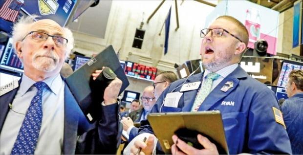 27일(현지시간) 미국 뉴욕증권거래소(NYSE)에서 주가가 급락하자 트레이더들이 전광판을 보며 놀란 표정을 짓고 있다.  /로이터연합뉴스