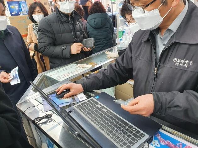 공적 마스크 '1인2매' 구매 제한 첫날인 6일 서울 종로 보령약국에서 직원이 구매자의 신분증을 확인하고 있다.