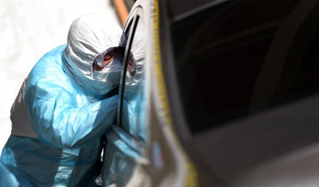 6일 부산 북구 드라이브스루 선별진료소에서 의료진이 의심환자의 검체 채취를 하고 있다.  /연합뉴스