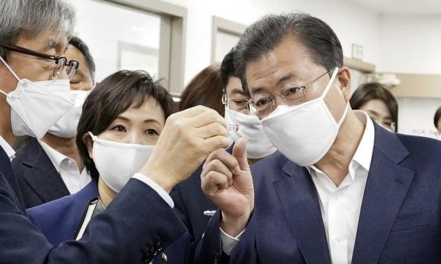 문재인 대통령이 25일 코로나19 진단시약 긴급사용 승인 기업 중 하나인 송파구 씨젠에서 시약 제품을 보고 있다. 2020.3.25 [사진=연합뉴스]