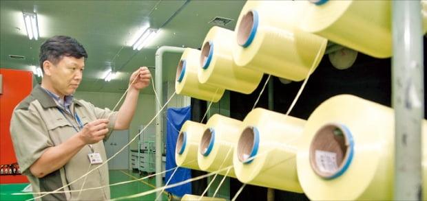 코오롱인더스트리 직원이 구미 공장에서 첨단 합성섬유 아라미드 제품인 헤라크론을 검사하고 있다.  코오롱 제공