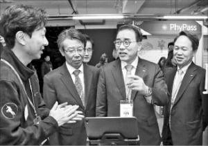지난해 서울 에스팩토리에서 열린 행사에서 조용병 신한금융 회장(왼쪽 세 번째)과 진옥동 신한은행장(네 번째)이 스타트업 관계자에게서 기술 설명을 듣고 있다. 신한금융 제공