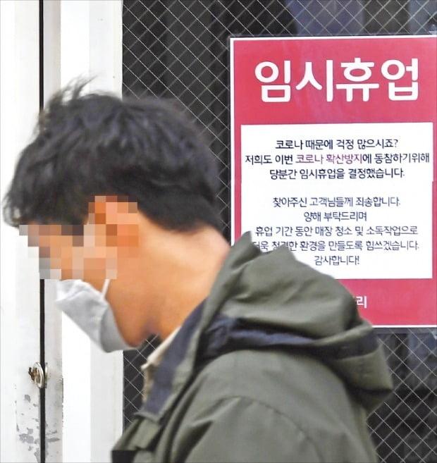 코로나19 여파로 소비시장이 위축되면서 자영업자의 줄도산 우려가 커지고 있다. 임시 휴업 안내문이 붙은 서울 명동의 한 카페 앞을 마스크를 쓴 행인이 지나가고 있다. 강은구 기자 egkang@hankyung.com