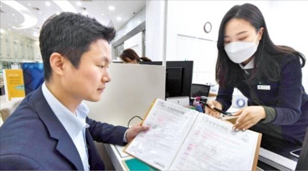 하나은행의 프라이빗뱅커(PB)가 마스크를 착용한 채 고객에게 금융상품을 설명해주고 있다. 하나은행은 2010년 금융권 최초로 유언대용신탁을 출시한 바 있다.  신경훈 기자 khshin@hankyung.com