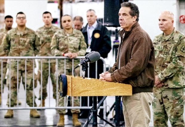 뉴욕주지사, 軍과 기자회견 앤드루 쿠오모 미국 뉴욕주지사가 23일(현지시간) 맨해튼에서 군 관계자와 함께 기자회견하고 있다. 뉴욕주에선 코로나19 확진자가 급증하면서 주방위군이 투입됐다.   EPA연합뉴스