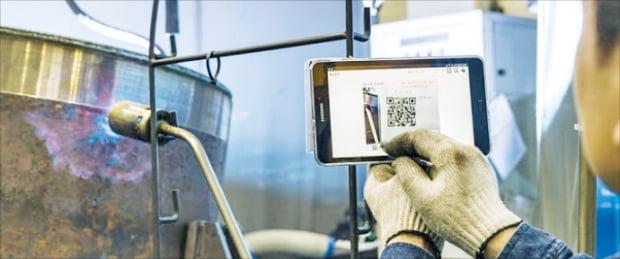 부산 강서구의 선박엔진부품 수리업체 종합폴스타 직원이 태블릿 PC로 제품을 확인하고 있다.  포스코 제공