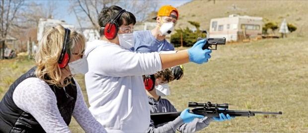 < 확진자 늘어나는 美…총기류 판매 급증 > 미국에서 코로나19 확진자가 급증하면서 비상사태에 대비한 총기류 판매도 가파르게 늘고 있다. 24일(현지시간) 미국 콜로라도주 러브랜드 외곽에서 사격 연습이 이뤄지고 있다.   /로이터연합뉴스
