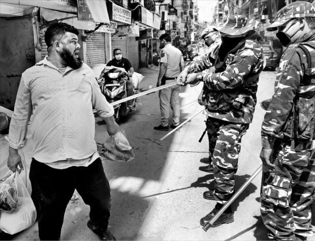 """< """"외출 하지마"""" 매질하는 인도 경찰 > 인도 정부는 코로나19 확산을 막기 위해 지난 24일 전국을 봉쇄하고 전 국민에게 외출 금지령을 내렸다. 25일 인도 뉴델리에서 경찰이 거리를 다니는 한 남성에게 매질을 하고 있다.  /로이터연합뉴스"""