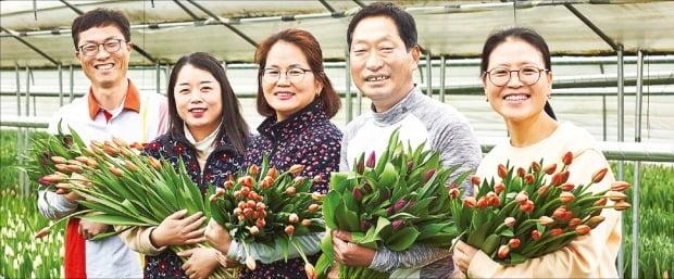 임동진 화림 대표(맨 왼쪽)와 협력 농장 농부들이 덜 핀 튤립을 수확한 뒤 들어 보이고 있다.  /마켓컬리 제공