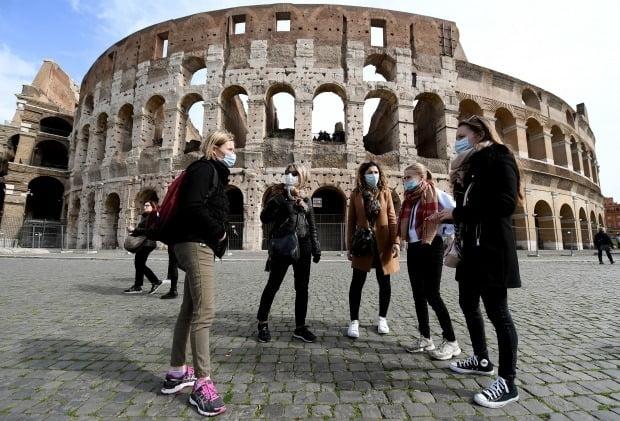 마스크를 쓴 관광객들이 로마의 명소 콜로세움을 구경하고 있다. 사진=연합뉴스