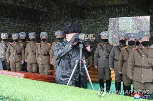 김정은 북한 국무위원장이 29일 동부지역 방어부대의 합동타격훈련을 지도했다고 29일 조선중앙통신에서 보고 있다. 김정은이 마스크를 쓰지 않은 채 망원경으로 훈련 현장을 보고 있다. /연합뉴스
