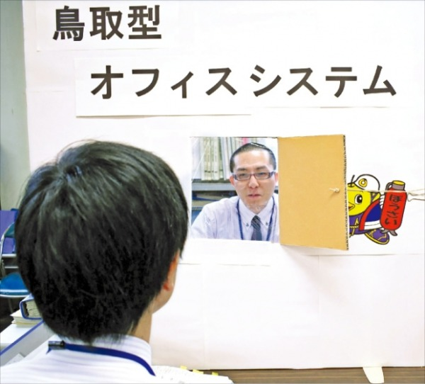 일본 돗토리현청 공무원들이 '돗토리식 오피스 시스템'이라고 써붙인 골판지 칸막이를 사이에 두고 업무를 하고 있다. 일본에선 최근 코로나19 환자가 빠르게 늘어나면서 '사회적 거리두기'가 확산하고 있다.   AFP연합뉴스