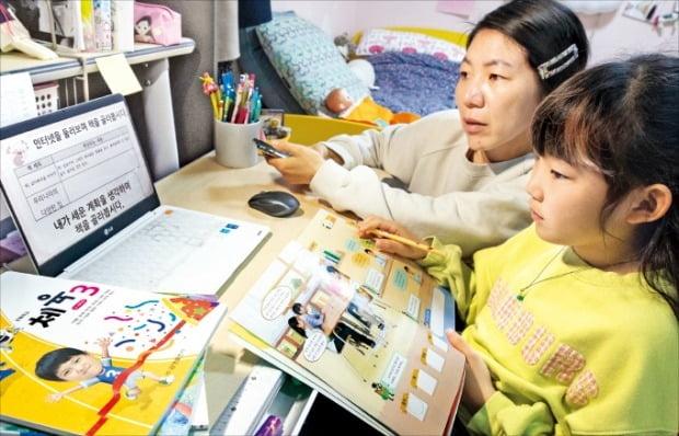 < 엄마의 개학 > 전국 초등학교 1~3학년이 20일 '3차 온라인 개학'에 마지막으로 합류했다. 이날 서울시내 한 가정에서 초등 3학년 학생이 엄마와 함께 원격수업을 듣고 있다.  뉴스1