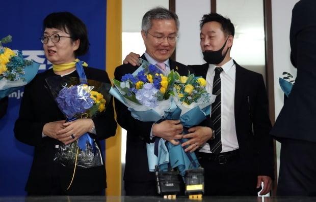 제21대 국회의원 선거 결과 기자회견에서 당선이 확정된 김진애(왼쪽부터), 최강욱 후보가 꽃다발을 받고 있다. 오른쪽은 정봉주 최고위원.  (사진=연합뉴스)