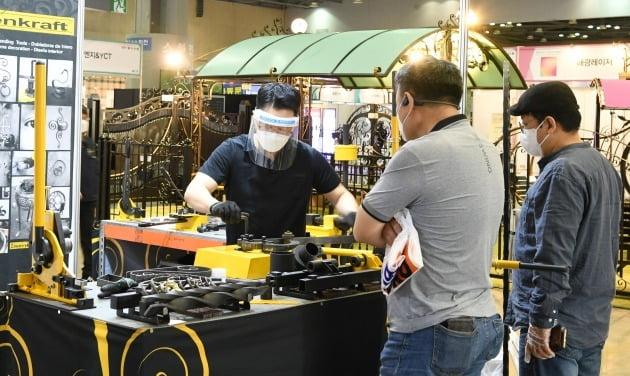 고양 킨텍스에서 열린 MBC 건축박람회 현장에서 방역 마스크에 얼굴 전체를 가리는 아크릴 보호대를 착용한 참여기업 직원이 관람객을 상대로 전시품을 시연하고 있다. / 킨텍스 제공.