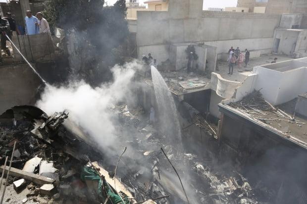 22일(현지시간) 파키스탄 남부 카라치의 여객기 추락 현장에서 소방대원들이 화재를 진압하고 있다. 이날 승객과 승무원 등 107명을 태운 파키스탄국제항공(PIA) A320 여객기가 카라치의 진나공항 인근 주택가에 추락했다. 2020-05-22 [사진=AP 연합뉴스]