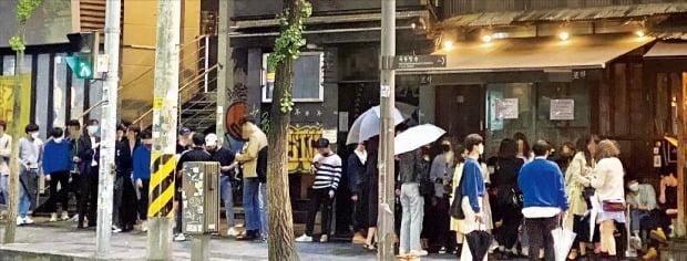 < 두 개의 긴 줄…흔들리는 생활방역 > 서울 이태원 클럽발(發) 신종 코로나바이러스 감염증(코로나19) 확진자가 빠른 속도로 증가하면서 10일 서울 용산구보건소 선별진료소는 검사를 받으려는 시민들로 북적였다(위). 중앙방역대책본부는 이태원 클럽 관련 코로나19 확진자가 54명에 달한다고 밝혔다. 이날 새벽 서울 홍대 인근 '헌팅 술집'에선 비가 내리는 날씨에도 세 시간 넘게 긴 대기줄이 이어지면서 '자율적 거리두기'가 지켜지지 않았다(아래).  김범준/최다은 기자 bjk07@hankyung.com