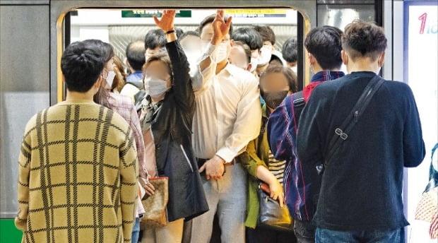 < 문 못닫을 정도 > 서울 지하철 마스크 착용 의무화가 시행된 13일 서울 동작구 사당역에서 마스크를 쓴 시민들이 출근길 만원 열차에 탑승하고 있다.  /뉴스1