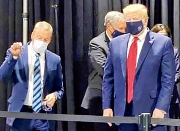 """< 마스크 쓴 트럼프…카메라에 잡혔다 > 미국 NBC방송은 도널드 트럼프 대통령이 21일(현지시간) 마스크를 쓰고 미시간주 포드자동차 공장을 둘러보는 사진을 입수해 보도했다. 코로나19 사태 이후 마스크를 착용한 트럼프 대통령의 모습이 공개된 것은 이번이 처음이다. 트럼프 대통령은 그동안 공개석상에서 마스크를 쓰지 않아 비판을 받았다. 이날도 언론 공개 일정 중에는 마스크를 착용하지 않았다. 그는 """"언론이 그것(마스크 착용 모습)을 보는 기쁨을 누리게 하고 싶지 않았다""""고 말했다.  /NBC방송 캡처"""