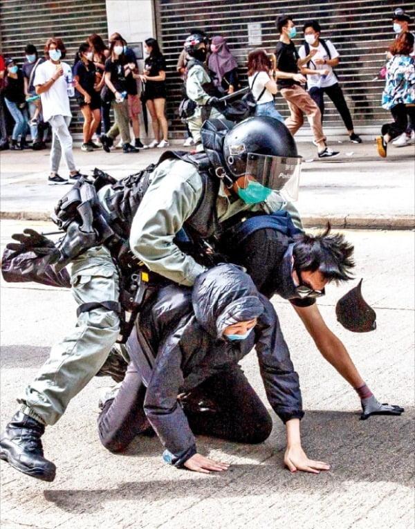< 시위대 진압하는 홍콩 경찰 > 홍콩 경찰이 지난 24일 코즈웨이베이지역 도로에서 범민주 진영의 시위 참가자들을 체포하고 있다. 수천 명의 시민은 이날 중국의 홍콩 국가보안법 제정에 반대하며 곳곳에서 대규모 집회를 열었다. 경찰은 이를 불법으로 규정하고 최루탄을 쏘며 강경 대응했다.  AFP연합뉴스