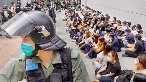 홍콩 경찰이 27일 도심에서 중국의 '홍콩 국가보안법' 제정에 반대하는 시위자들을 모아놓은 뒤 감시하고 있다. 중국 전국인민대표대회는 28일 전체회의를 열어 홍콩 내 반정부 활동을 처벌하는 홍콩 보안법을 표결에 부친다. /AP연합뉴스