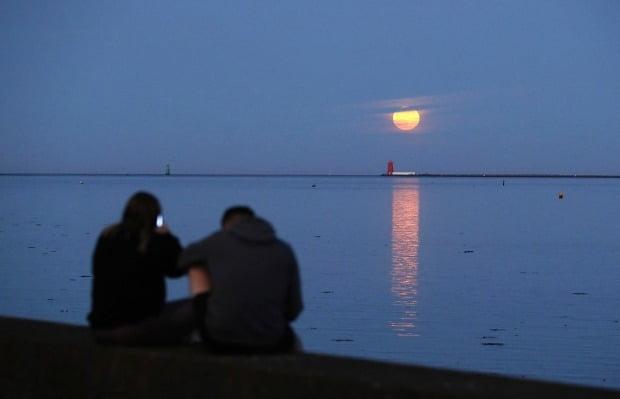 아일랜드 더블린 해변 풀베그 등대 위로 7일(현지시간) 보름달이 떠오르는 모습을 한 커플이 관찰하고 있다. AP연합뉴스