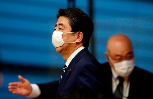 아베 신조(왼쪽) 일본 총리가 25일 마스크를 착용한 채 도쿄 총리관저의 기자회견장에 들어서고 있다. 사진=연합뉴스