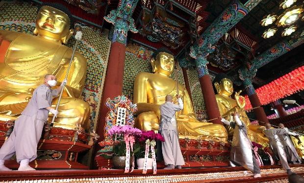 서울 종로구 조계사 대웅전에서 스님들이 부처님오신날 봉축법요식을 앞두고 대청소를하며 삼존불의 먼지를 털어내고 있다.(사진=연합뉴스)
