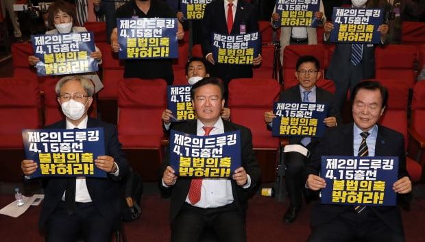 민경욱 미래통합당 의원(앞줄 가운데)이 11일 오후 서울 여의도 국회 의원회관에서 열린 '4.15총선 개표조작 의혹 진상규명과 국민주권회복대회'에서 참석자들과 함께 피켓을 들고 구호를 외치고 있다. 사진=뉴스1