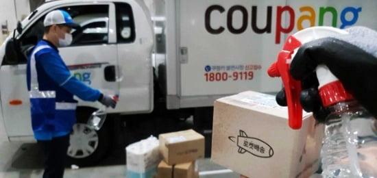 쿠팡 자체 배송직원(쿠팡맨)이 '로켓배송' 상품 상자를 휴대용 살균제로 소독하는 모습. 사진=쿠팡 제공