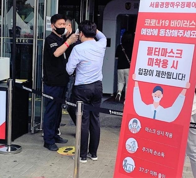 이달 4~7일 대치동 세텍(SETEC)에서 열린 '서울경향하우징페어'를 찾은 관람객이 전시장 입구에서 발열검사를 받고 있다. 현장에서는 전체 관람객을 대상으로 실명제, 마스크 및 비닐장갑 착용, 발열검사 등 4~5단계의 방역조치가 이뤄졌다.