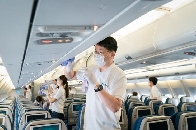 29일 대한항공에 따르면 조원태 한진그룹 회장은 이날 서울 강서구 대한항공 본사 격납고에서 대한항공 임직원들이 직접 손걸레로 기내를 소독하는 작업에 동참했다.  사진=대한항공 제공