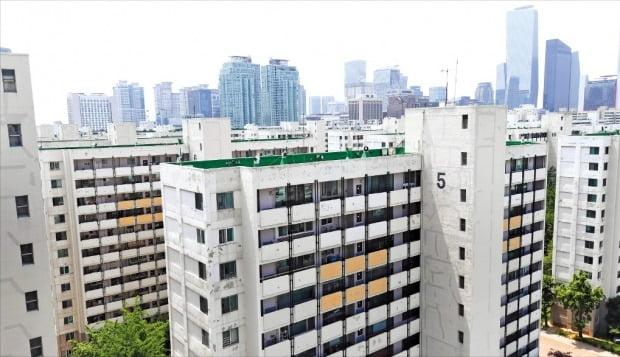 < 여의도 고층 빌딩 앞 낡은 아파트 > 1971년 준공돼 여의도에서 가장 오래된 시범아파트. 서울시의 여의도 개발 마스터플랜 발표가 보류되면서 재건축 사업이 2년 가까이 진행되지 않고 있다.  김범준 기자 bjk07@hankyung.com